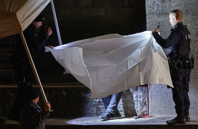 Swiss police hold a tarp over a dead body following the shooting death of three people at a local Islamic center in December of 2016.