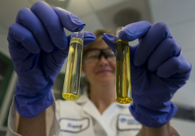 A lab technician holds up two vials of fish oil.