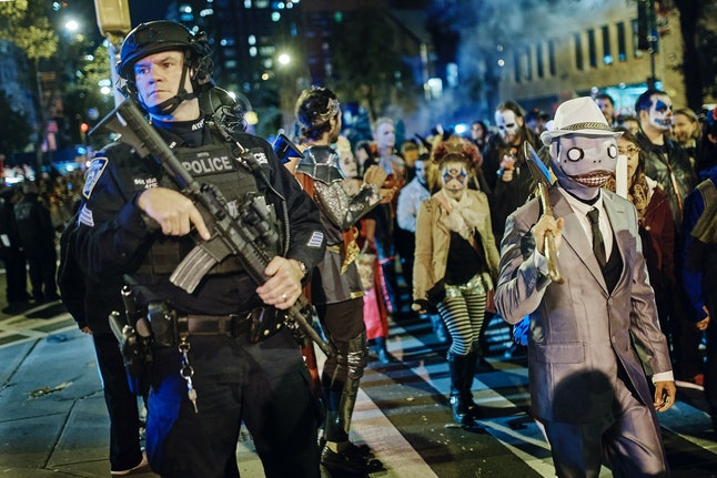 Heavily armed police stand guard as revelers march during the Greenwich Village Halloween Parade, Tuesday, Oct. 31, in New York.