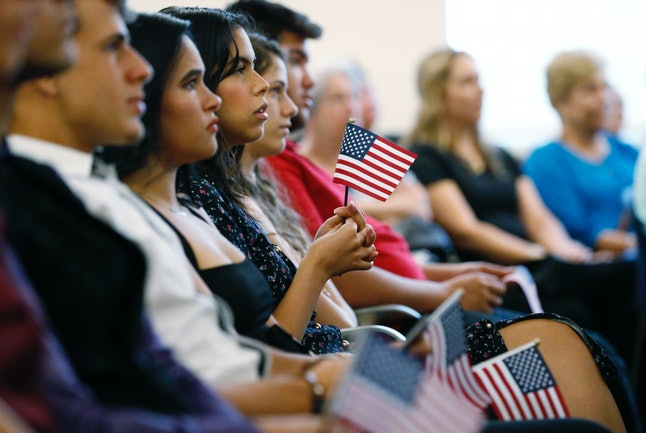 New citizens hold American flags as they listen during a naturalization ceremony in August