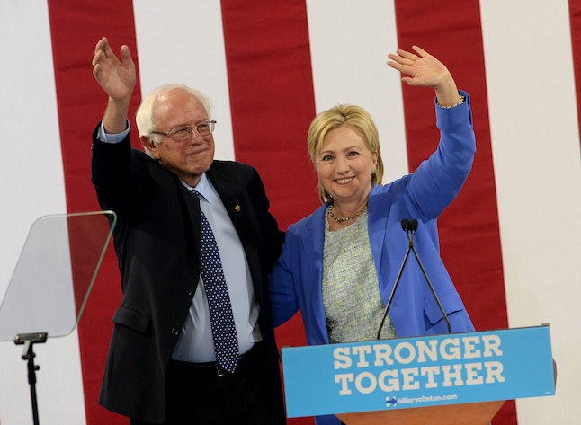 Sanders waves with Clinton to the crowd while campaigning for his former rival in New Hampshire.