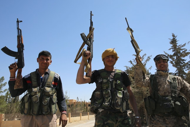 Pro-Assad rebels celebrate after regaining control of al-Qaryatayn from ISIS.