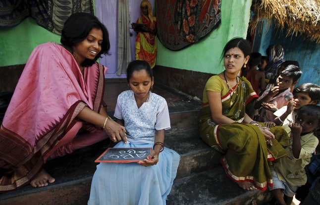 A woman taught a young girl in India during International Literacy Day on September 8, 2014.