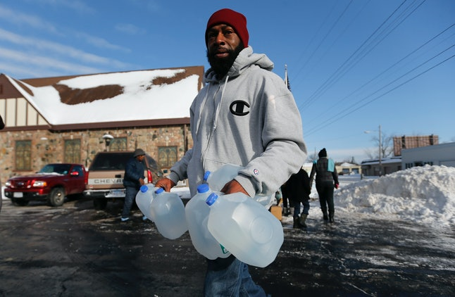 Flint resident Lemott Thomas carrying bottled water distributed by a church in February 2015.