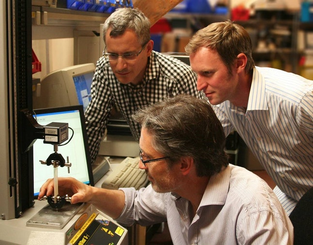 Strutt, at right, and team members in the lab
