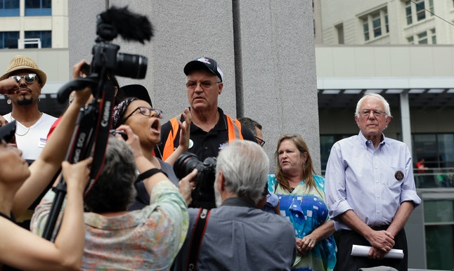 Marissa Johnson, left, continues to speak while surrounded by media members as Democratic presidential candidate Sen. Bernie Sanders, I-Vt., looks on at right before leaving the stage at a rally Saturday, Aug. 8, 2015, in downtown Seattle.