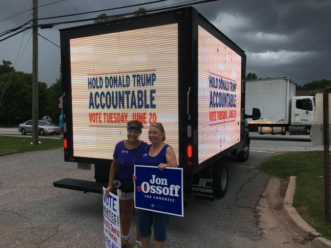 Two Jon Ossoff supporters pose in front of a truck paid for by the Ossoff campaign on Monday.