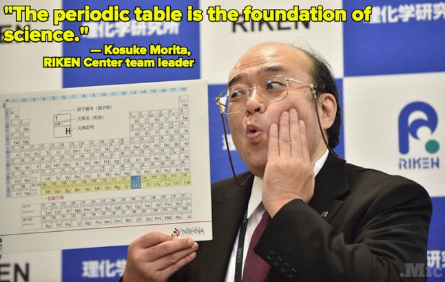 Kosuke Morita, leader of the RIKEN Center team, which discovered element 113, holds up a periodic table during a press conference on Thrusday.