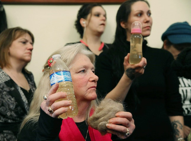 Flint residents hold up bottles of tainted water at an oversight committee hearing in Washington, D.C., on Feb. 3.