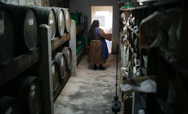 A nun walking through the wine cellar at her convent in Bolivia.