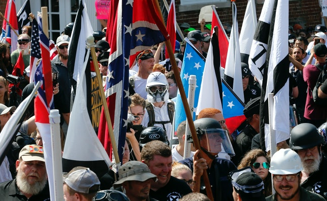 White nationalist demonstrators walk into the entrance of Lee Park surrounded by counter demonstrators in Charlottesville on Saturday.