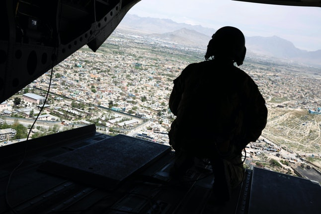 A soldier holds a gun while traveling in the back of a helicopter bound for Kabul, Afghanistan.
