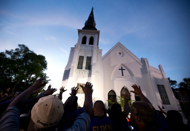 People stretch there hands toward Emanuel AME Church in Charleston, during a vigil in 2015.
