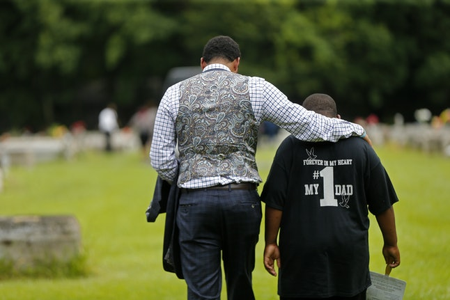 Family attorney Justin Bamberg, left, comforts Na'Quincy, 10, son of Alton Sterling, after Alton's burial.