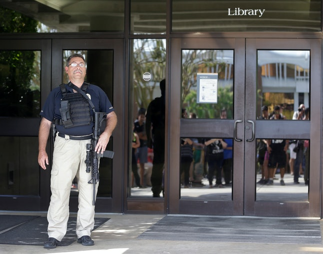 A police officer stands guard outside the entrance to the library.