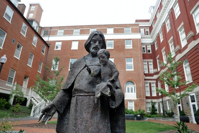 A Jesuit statue is seen in front of Freedom Hall, formerly named Mulledy Hall, on the Georgetown University campus.