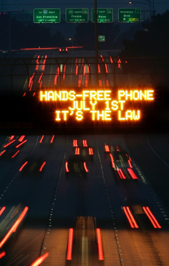 A traffic sign warns drivers not to use hand-held phones while driving.