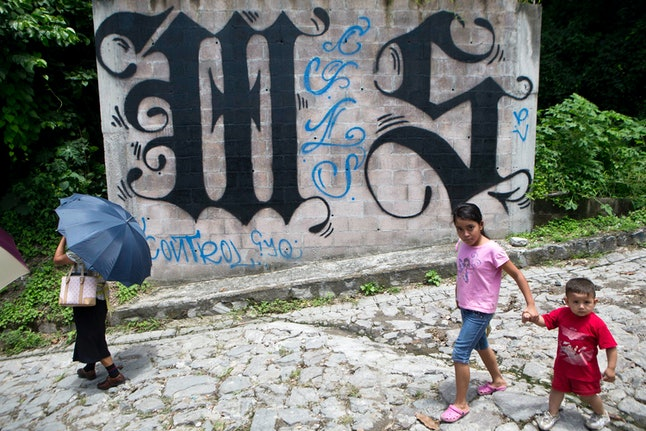 A family walks by a wall covered with a symbol from the Mara Salvatrucha, or MS-13, gang in El Salvador.