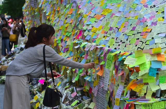 South Koreans leave messages written on sticky notes at Gangnam subway station on May 20, 2016. The memorial is for a 23-year-old woman who was stabbed to death by a stranger the previous night in a nearby public bathroom.