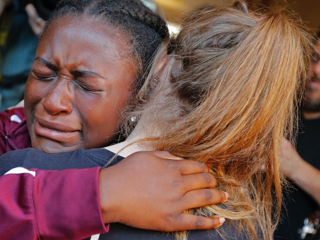 Friends hug before a vigil for the victims of the shooting at a Florida high school Wednesday that left 17 dead and more than a dozen others injured.