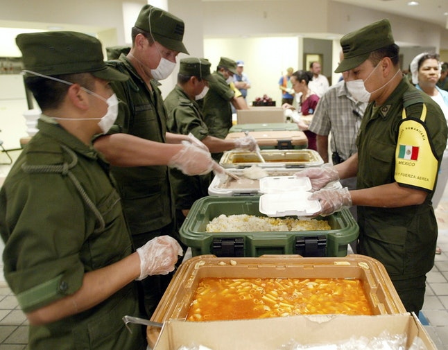 Mexican soldiers prepared plate of food for Hurricane Katrina evacuees in 2005.