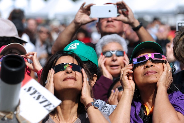 People look through eclipse viewing glasses, telescopes or photo cameras an annular solar eclipse, on Sept. 1, 2016, on the Indian Ocean island of La Reunion.