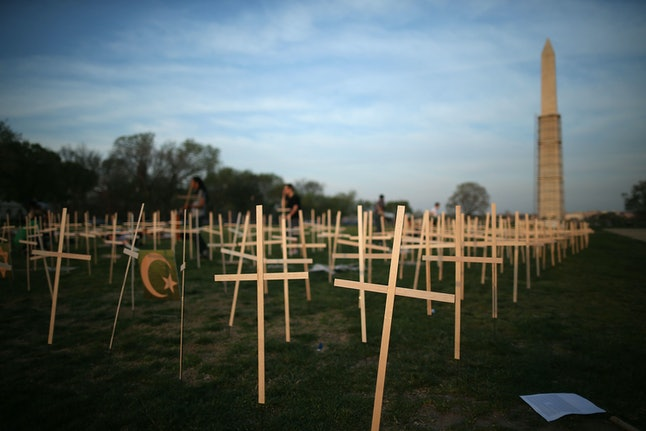 Volunteers place grave markers on the National Mall as over 3,300 crosses, stars of David, and other religious symbols are placed to remember those affected by gun violence, on April 11, 2013.