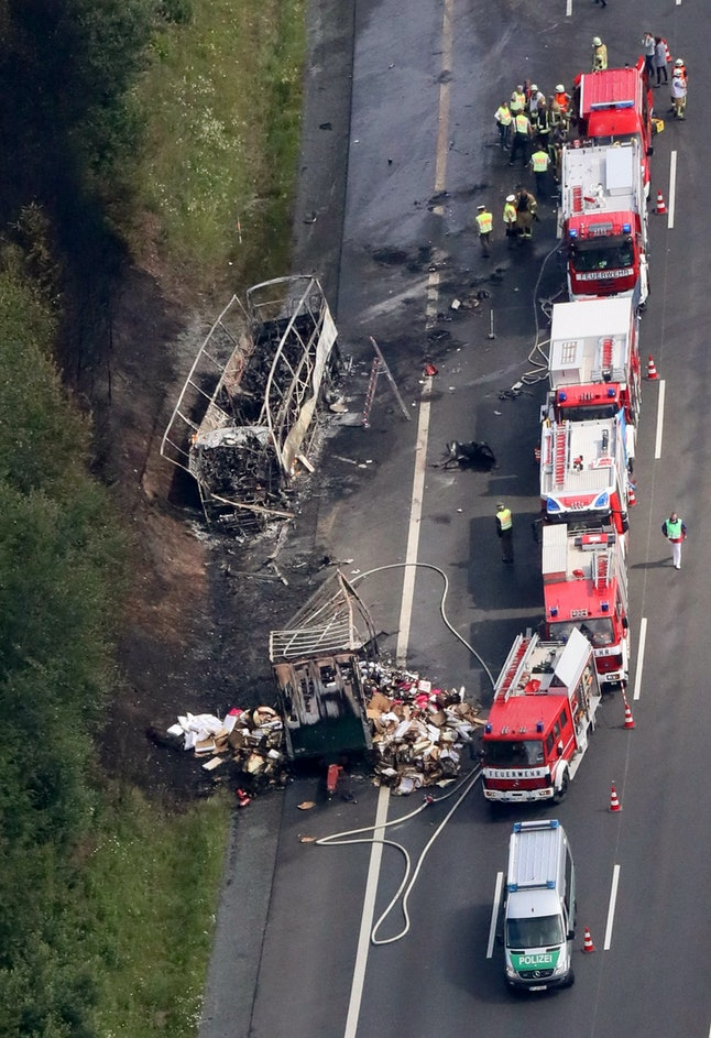 Aerial view shows firefighters at work at the scene where a tour bus burst into flames following a collision with a trailer truck on the highway A9 near Münchberg, Germany.