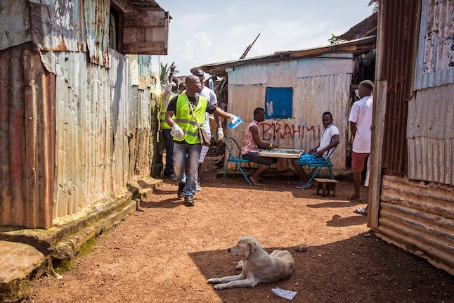 A health worker volunteer walks past residents as they distribute bars of soap and information about Ebola in Freetown, Sierra Leone, Saturday, Sept. 20, 2014.