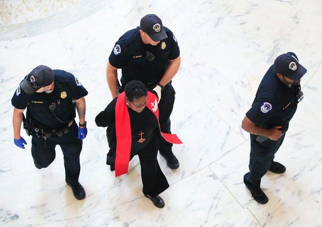 Police arrest a minister protesting Republicans' Affordable Care Act repeal efforts on July 18.
