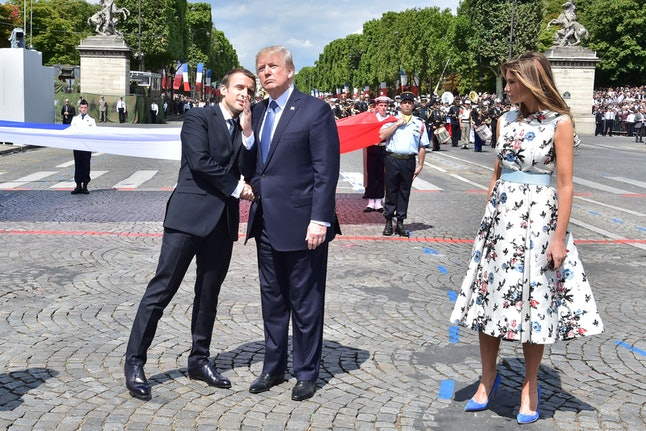 French President Emmanuel Macron shakes hands with Donald Trump, next to first lady Melania Trump, during the Bastille Day military parade in Paris on July 14.