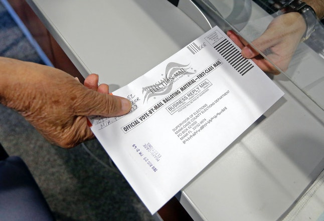 A Florida voter hands in his absentee ballot in the 2016 primaries