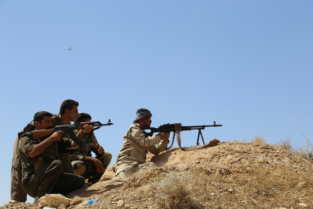 Kurdish Peshmerga forces fight against IS to regain control of the town of Calavle, Iraq, on Sunday.