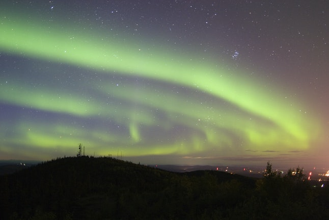 Take in the mesmerizing Northern Lights from a peaceful lookout point above Fairbanks.