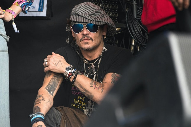 Johnny Depp sits at the side of the Pyramid Stage watching Run the Jewels perform on day tree of the Glastonbury Festival 2017 at Worthy Farm, Pilton on June 24, 2017 in Glastonbury, England.