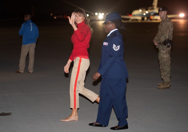 Melania Trump waves after disembarking from a military aircraft upon arrival at Joint Base Andrews in Maryland, early on Oct. 7, following a six-day, four-country tour of Africa.