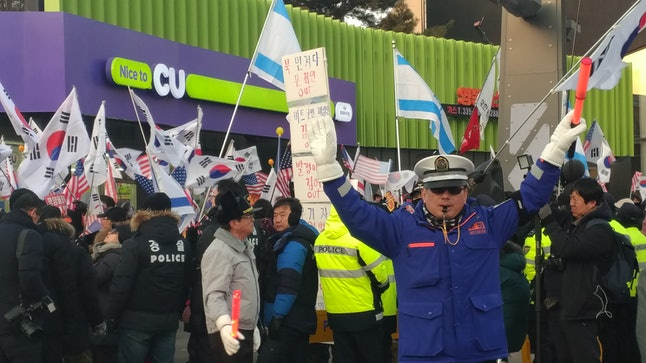A police officer guides traffic in a crowd of mixed demonstrators, some of whom were calling for peace while others protested South Korean President Moon Jae-in and the presence of North Koreans at the Olympics.