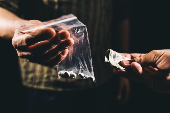 Someone offers another person money in exchange for a bag of pills.