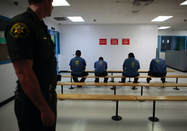 A group of detainees is overseen by law enforcement