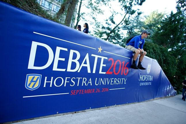 A student sits on a sign at Hofstra University, site of the first presidential debate between Clinton and Trump