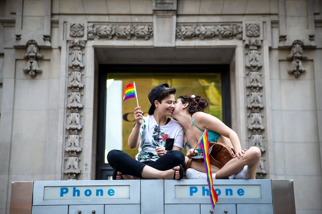 A couple watches the New York City Pride March, June 26, 2016 in New York City.