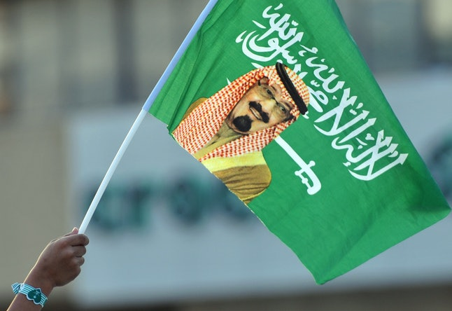 A Saudi child holds up a national flag with picture of King Abdullah bin Abdulaziz during celebrations marking the 83rd Saudi Arabian National Day in Riyadh.