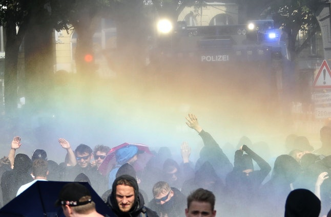 A police water cannon sprays water onto demonstrators who blocked a road in Hamburg.