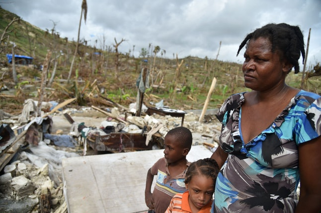 Jaqueline and her children stand on the site of their destroyed home amid destruction from Hurricane Matthew.