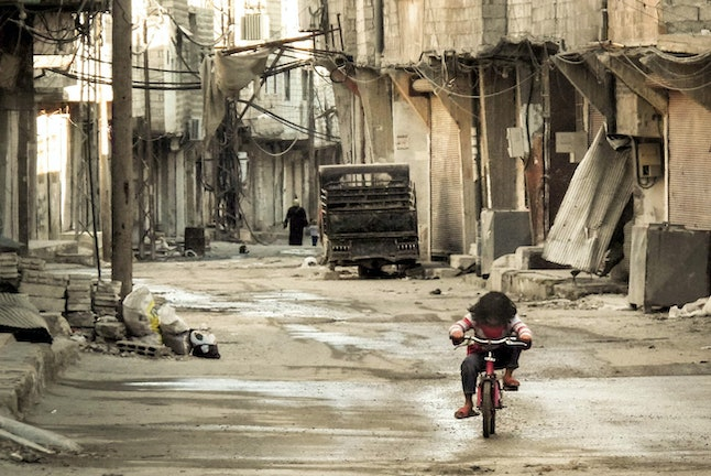 A Syrian girl rides her bicycle in the Teshrin neighborhood of the Qabun area in Damascus on January 3, 2013