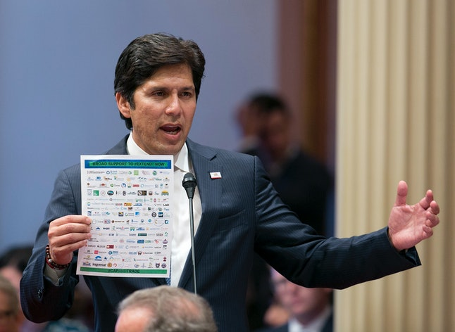 Senate president pro tem Kevin de Leon displays a list of various backers of a climate change bill Monday.