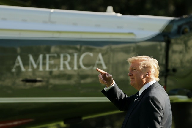 U.S. President Donald Trump points as he walks across the South Lawn before departing the White House.
