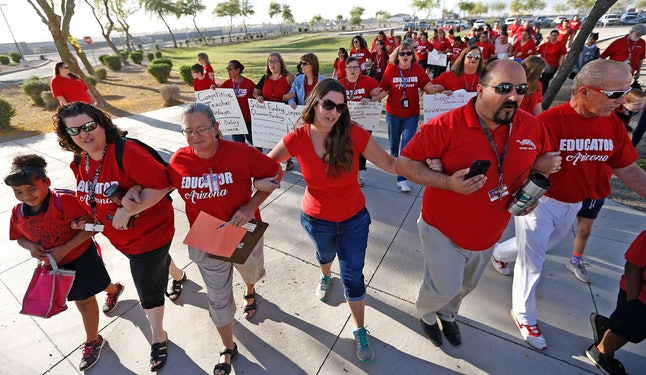 "Teachers walk arm-in-arm with students and parents into Tuscano Elementary School as they stage a ""walk-in"" for higher pay and school funding on April 11 in Phoenix."