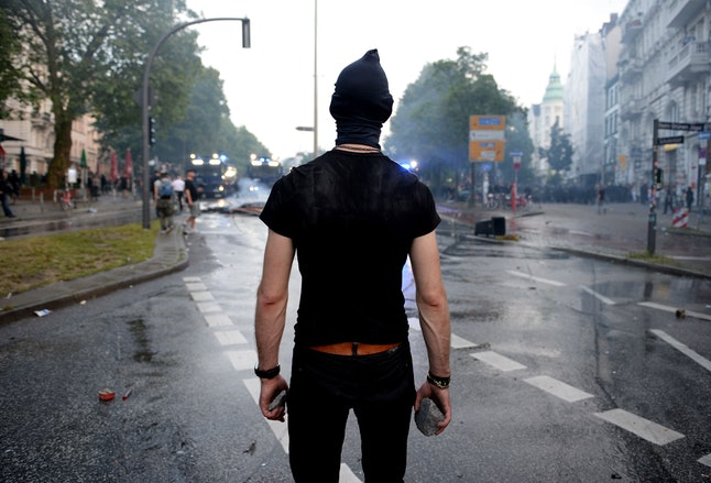 A protester carrying rocks looks at riot police on July 7 in Hamburg.
