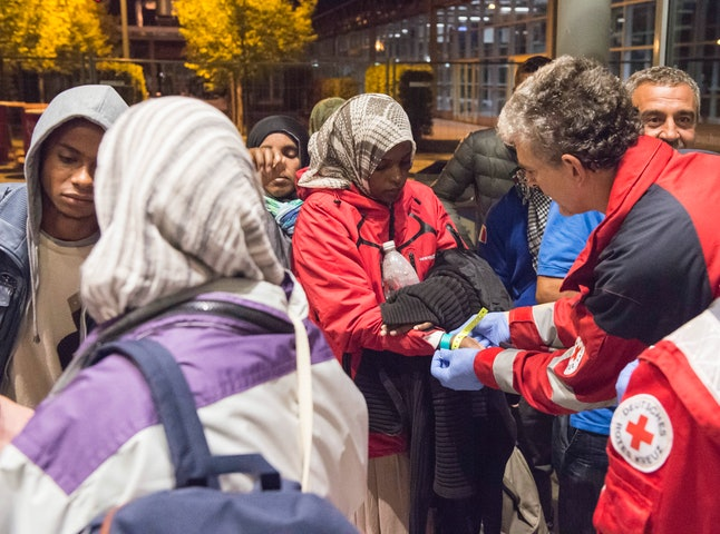 German officials in Munich provide refugees with ID tags and shelter upon arrival.